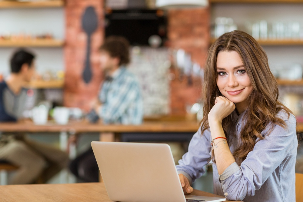 Attractive positive young curly female in grey shirt using laptop in cafe.jpeg